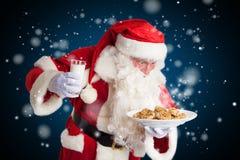 Santa Claus är lycklig mjölkar omkring och kakor royaltyfri foto