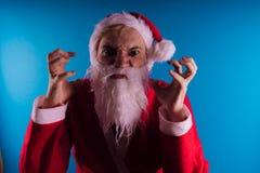 Santa Claus émotive sur un fond bleu Le concept de mauvaise Santa Claus Bonne année et Joyeux Noël ! images libres de droits