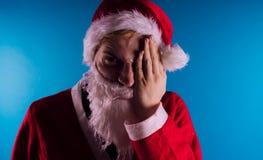 Santa Claus émotive sur un fond bleu Le concept de mauvaise Santa Claus Bonne année et Joyeux Noël ! image libre de droits