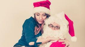 Santa Claus étreignant la femme avec le chapeau christmassy photo stock
