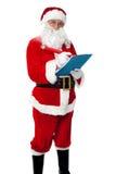 Santa Claus делая список получателей подарка Стоковая Фотография