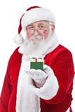 Santa Claus держа и предлагая подарок Стоковые Фото