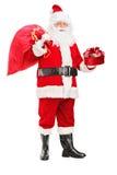 Santa Claus держа мешок и подарок Стоковая Фотография