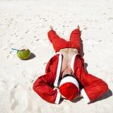 Santa Claus на пляже ослабляя Стоковые Изображения RF