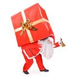 Santa Claus носит большой подарок Стоковая Фотография RF