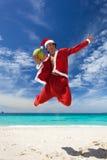 Santa Claus скачет с кокосом на пляже Стоковое Изображение