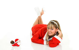 Santa Claus. Young blond girl in Santa Claus dress. Playing with her toy Royalty Free Stock Images