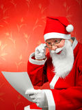 Santa claus. Cheerful santa reads the letter Stock Image