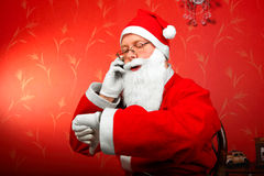Santa claus. Talking on mobile phone and looking on the watch stock image