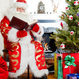 Santa Claus. Santa sitting at the Christmas tree, fireplace and reading a book stock photography