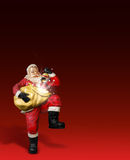Santa Claus. Statue holding bag on red background Royalty Free Stock Images