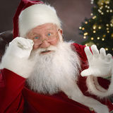 Santa Claus. Close up looking into camera, waving and talking to us, square, festive background, focus in foreground Royalty Free Stock Photography