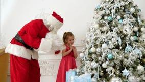 Santa Claus aidant la fille assez petite à décorer l'arbre de Noël clips vidéos