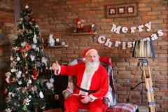 Santa Claus alegre muestra placer del sitio adornado con holida Imágenes de archivo libres de regalías