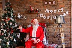 Santa Claus alegre muestra placer del sitio adornado con holida Foto de archivo