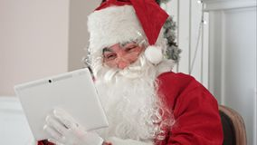Santa Claus alegre que comprueba encima de correos electrónicos de la Navidad de niños en su tableta digital fotografía de archivo libre de regalías