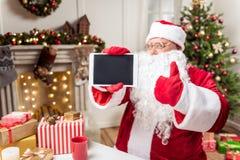 Santa Claus alegre que muestra el dispositivo digital como regalo Imágenes de archivo libres de regalías