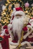 Santa Claus als Spielzeug im roten Klagenkostüm in einer Kappe und gold-eingefaßte Gläser mit erröten auf den Backen tragen Gesch lizenzfreies stockbild