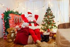 Santa Claus als voorzitter in de ruimte met de Kerstboom en F stock afbeeldingen
