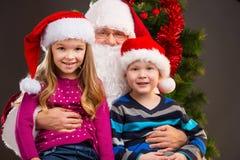 Santa Claus amável idosa que guarda duas crianças em seus joelhos. imagens de stock royalty free