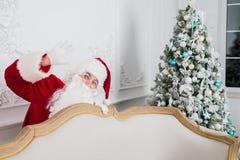 Santa Claus anseende bak en julgran och en soffa som ser kameran Royaltyfria Foton