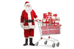 Santa Claus anseende med gåvor i en shoppa vagn arkivbilder