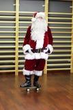 Santa Claus anseende på skateboarden i konditionstudio Royaltyfri Bild