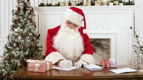Santa Claus answering Christmas letters in his workshop stock video