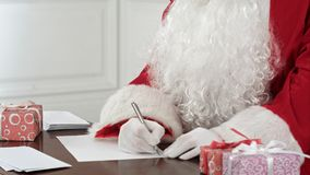 Santa Claus answering Christmas letters sitting at his table. Closeup shot. Professional shot on BMCC RAW with high dynamic range. You can use it e.g. in your Royalty Free Stock Photo