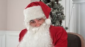 Santa Claus answering Christmas letters and talking to a camera Stock Image