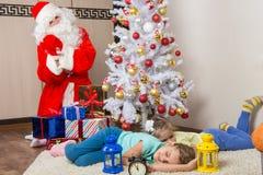 Santa Claus a apporté des cadeaux pendant de nouvelles années Ève et a ramolli des visages des deux soeurs de sommeil Images stock