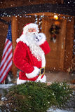Santa Claus apportent l'arbre de Noël dans la maison dans le secret Image libre de droits