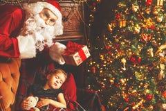Santa Claus apresenta o presente do Natal à menina de sono da criança no Ch imagens de stock royalty free