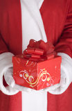 Santa Claus arm with present Royalty Free Stock Images