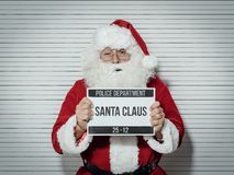 Santa Claus mug shot. Santa Claus arrested on Christmas eve, he is posing for his mug shot at the police department and holding an identification board Royalty Free Stock Photo