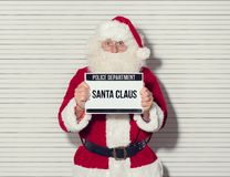 Santa Claus mug shot. Santa Claus arrested on Christmas eve, he is posing for his mug shot at the police department and holding an identification board Royalty Free Stock Photos