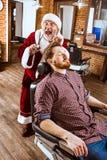 Santa claus as master at barber shop Royalty Free Stock Photo