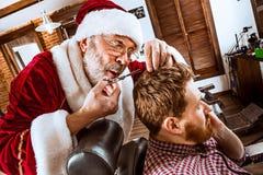Santa claus as master at barber shop Royalty Free Stock Photography