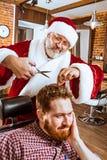Santa claus as master at barber shop Stock Photography