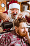 Santa claus as master at barber shop Stock Image