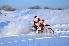 Santa Claus astride on the motocross bike Stock Image