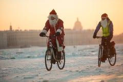 Santa Claus auf einem Fahrrad mit einem Akkordeon stockfotos