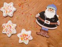 Santa Claus auf einem Hintergrund von hellen Bällen und von Plätzchen in der Glasur Lizenzfreie Stockfotografie