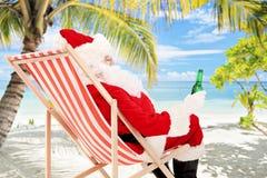 Santa Claus auf einem trinkenden Bier des Stuhls und Genießen auf einem Strand Lizenzfreie Stockfotografie
