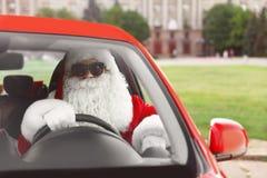 Santa Claus auténtica en las gafas de sol que conducen el coche imagen de archivo