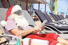 Santa Claus authentique à l'aide du comprimé sur la chaise longue images stock