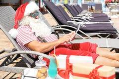 Santa Claus authentique à l'aide du comprimé sur la chaise longue photos libres de droits