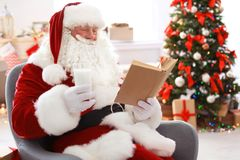 Santa Claus authentique avec le verre du livre de lecture de lait image libre de droits