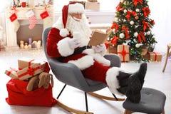 Santa Claus authentique avec le verre du livre de lecture de lait photographie stock libre de droits