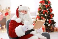 Santa Claus authentique avec le verre du livre de lecture de lait photos stock